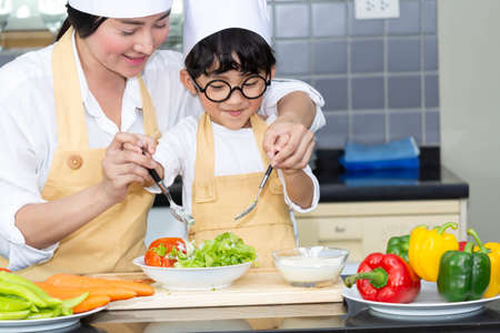 Asian woman young mother with son boy cooking salad food with vegetable holding tomatoes and carrots, bell peppers on plate for happy family cook food enjoyment lifestyle kitchen in home