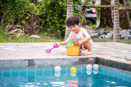 Asian boy son children playing pool toys Poolside happy Learning life with family Fun to learn and play. Standard-Bild