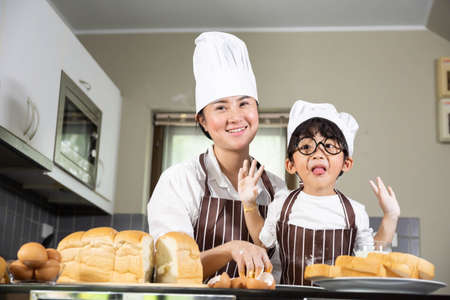 Asian mother and the son cooking white flour Kneading bread dough motherteaches children practice baking ingredients bread, egg on tableware in kitchen lifestyle happy Learning life family Fun  learn