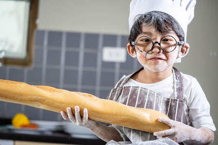 Asian Boy wear glasses cooking with white flour Kneading bread dough teaches children practice baking ingredients bread, egg on tableware in kitchen lifestyle happy Learning life with family Fun to learn Standard-Bild