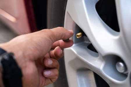 Asian man car inspection Measure quantity Inflated Rubber tires car.Close up hand holding machine Inflated pressure gauge for car tyre pressure measurement for automotive, automobile image Standard-Bild