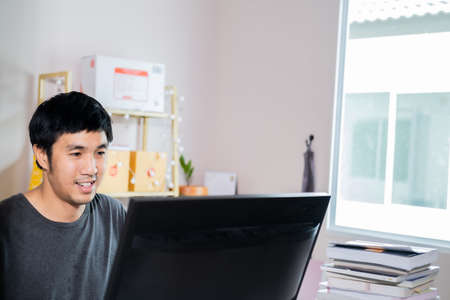 Asian man administrator staff call center in home service office assistance work from home looking data customer from computer communication during virus