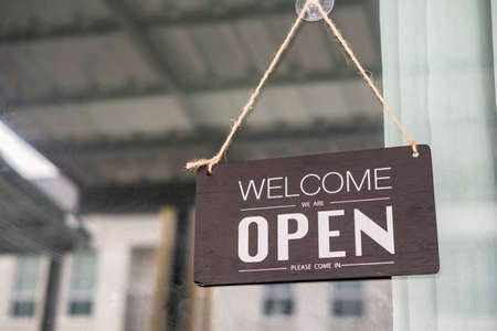 Asians with sign open and closed in restaurant for lockdown ideas unlock freedom tourist travel for lifestyle customer sign open and closed welcome new normol during virus disease  unlock lockdown Standard-Bild