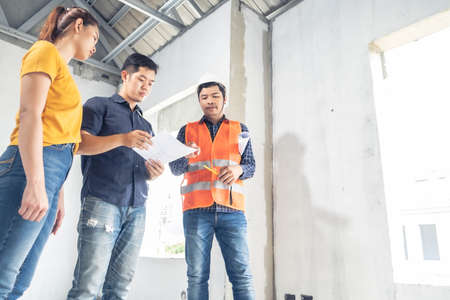 Young asian couple checking house with foreman engineering home inspection building house Walk home inspection with looking and pointing construction for check building home on job site to construction 2021