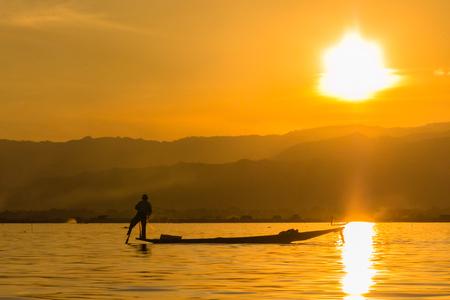 Fisherman with Leg rowing during Sunset,  inle lake in Myanmar  Burmar  Stock Photo - 29486257