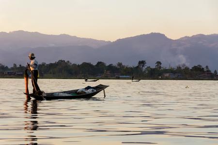 Fisherman with Leg rowing during Sunset,  inle lake in Myanmar  Burmar  Stock Photo - 29666330