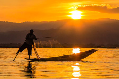 Fisherman with Leg rowing during Sunset,  inle lake in Myanmar  Burmar  photo