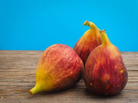 Fresh fig fruit on wooden old boards with a blue background