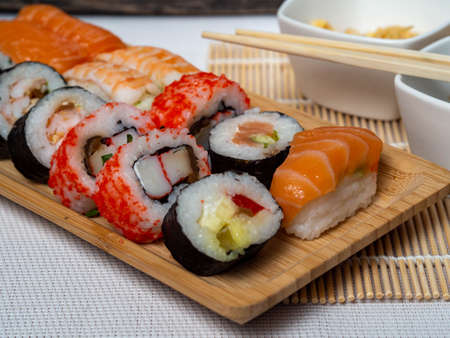 Japanese sushi food. Maki ands rolls with tuna, salmon, prawns, crab, and avocado. Top view of a variety of sushi. Colorful roll of sushi, uramaki, hosomaki and nigiri on wooden trays. Archivio Fotografico