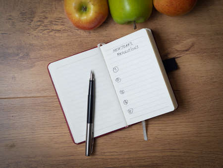 A small notebook with marked places for New Year's resolutions lying on a wooden table, with three fresh and beautiful apples lying next to it. there is a fountain pen on the notebook
