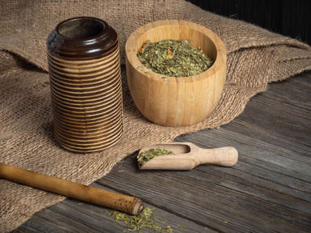 American hot herbal drink. Yerba mate, herbal mate in a clay cup with bombilla on a wooden background