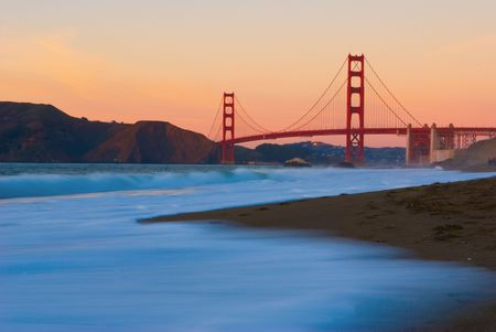 This photograph of golden gate bridge was taken from baker beach at sunset.This photograph shows the bridge with nice red colors and a silk like foreground of pacific ocean. 版權商用圖片
