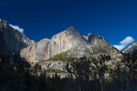 Upper and lower Yosemite falls amidst mountains.