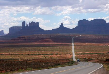 conveys: Monument valley park in Utah.  A car in the photograph conveys scale.