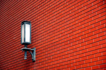 A lamp in the red brick wall.