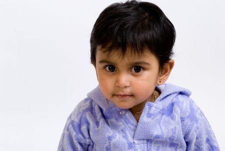 This is a curious indian toddler looking at the viewer.