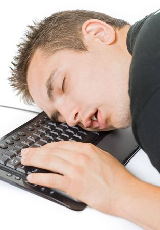 Young tired man sleeping on the keyboard photo