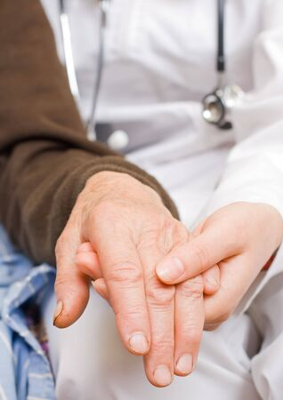 Young doctor holds old lady's hand Stock Photo - 6667316