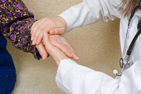 positiveness: The doctor holding an elderly womans hand.
