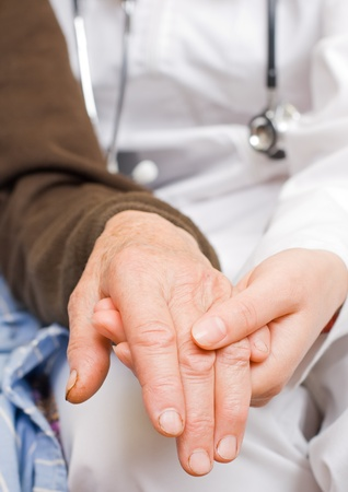 positiveness: Young doctor holds old ladys hand