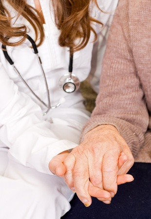 caring hands: Young doctor holds old man