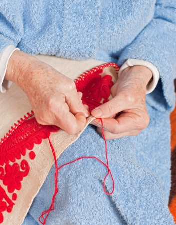 old age care: Old woman sitting on the bed, and sewing