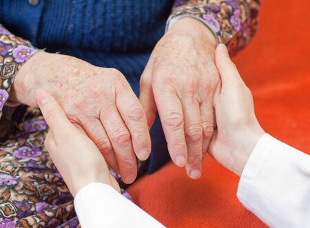 assisting: Young doctor holds the old womans hand