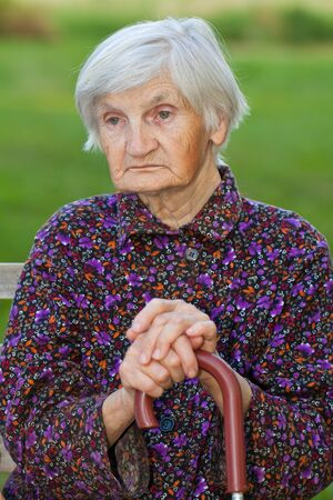 Elderly lonely woman in the nature photo