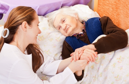 nursing: Young doctor holds the old womans hands