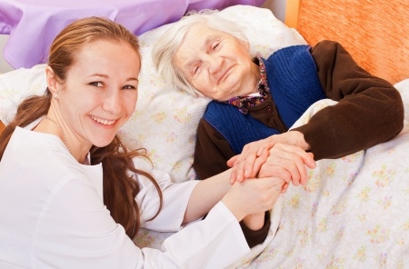 Young doctor holds the old womans hands photo