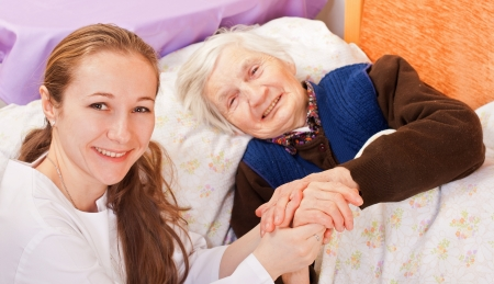 Young doctor holds the old womans hands