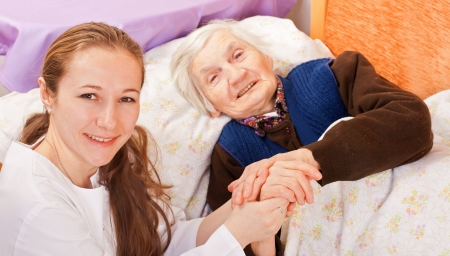 woman's: Young doctor holds the old womans hands