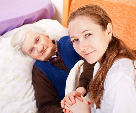 Young doctor holds the old woman's hands Stock Photo - 18068698