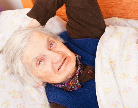 Elderly lonely woman in the bed photo