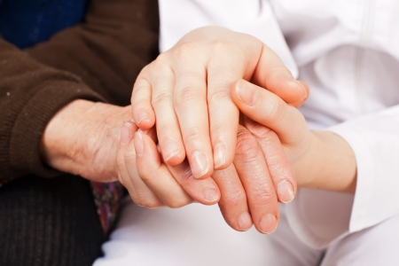 Young sweet doctor holds the old woman hands photo