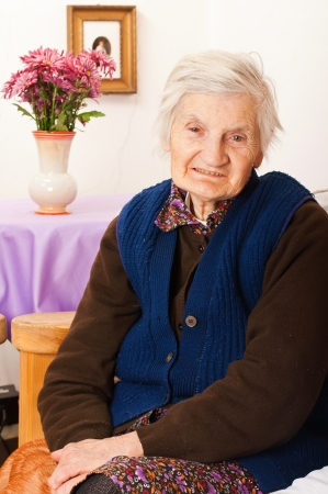 Elderly woman sits on the bed Stock Photo - 18068710