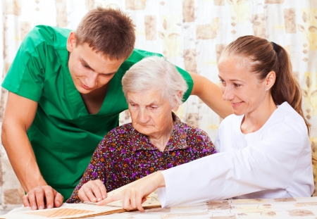 old carer: Elderly woman with the sweet young doctors Stock Photo