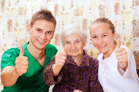 carer: Elderly woman with the sweet young doctors Stock Photo