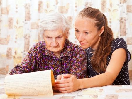 Dulce dama joven sostiene la mujer de edad avanzada