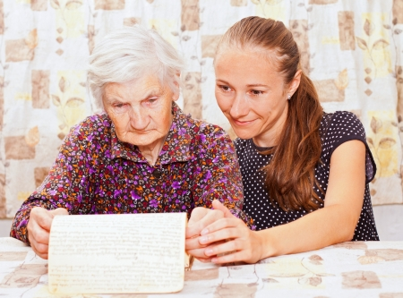 Young sweet lady holds the elderly woman photo