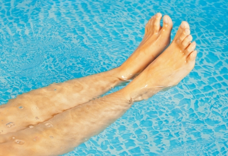 long toes: Young sweet womans feet in a swimming pool