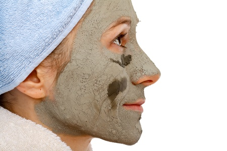 Cosmetics mask of clay on the beautiful young female face photo