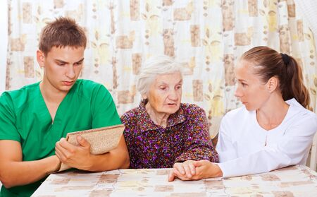 nursing care: Elderly woman with the sweet young doctors Stock Photo