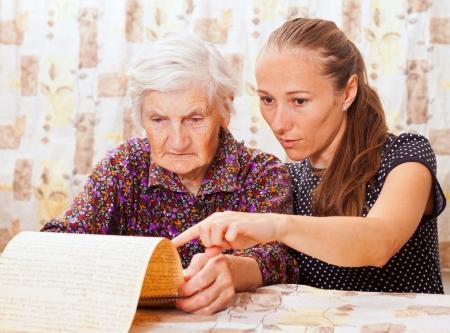 Dulce dama joven sostiene la mano de la anciana