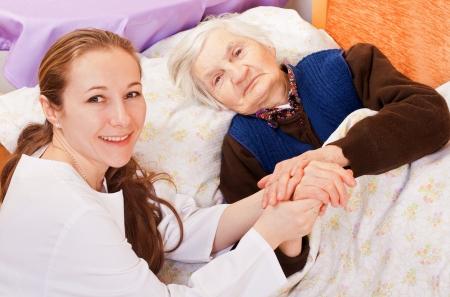 Joven médico sostiene las manos de la anciana