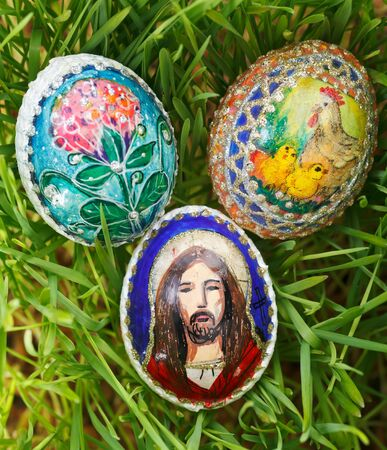 Colorful painted easter eggs between growing green wheat photo