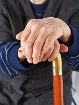 Elderly hands resting on the walking stick Stock Photo - 18575073