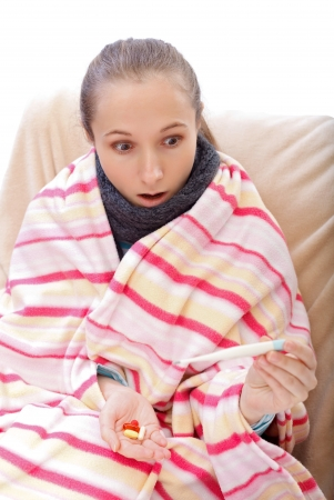 pharyngitis: Young woman suffering from influenza and scared from the high temperature Stock Photo