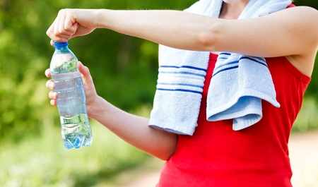 hand holding bottle: Do not forget to hydrate yourself during workout