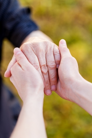 Young doctor hold elderly hands   Stock Photo